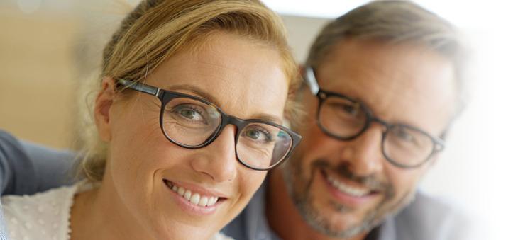Frau und Mann tragen Brille und lächeln.