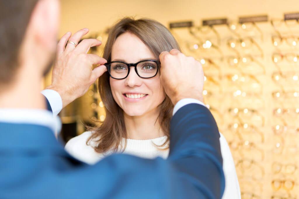 Optiker passt Kundin eine Brille an.