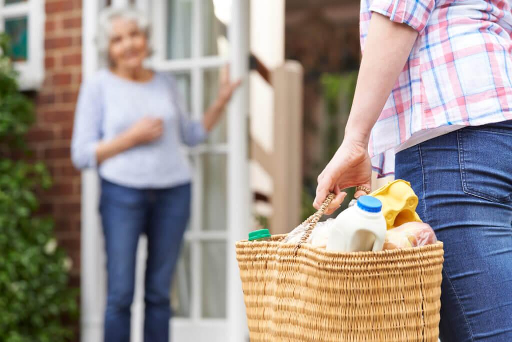 Frau trägt vollen Einkaufskorb zu Seniorin.