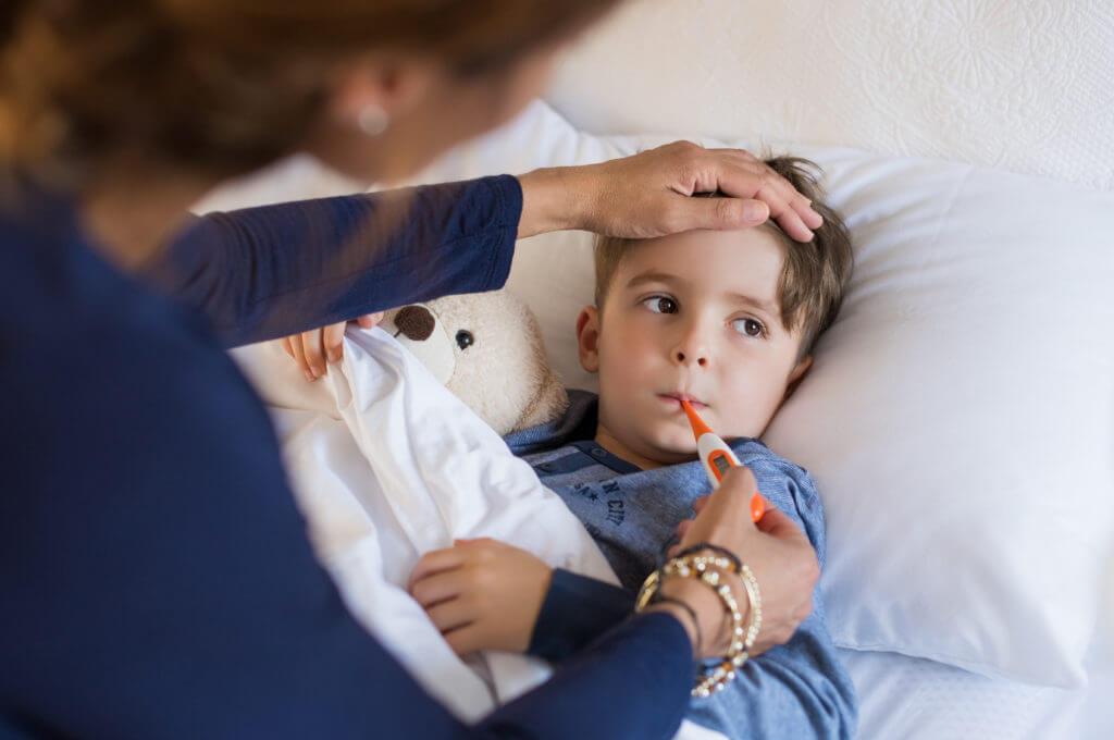 Frau misst Fieber bei Kind im Bett.