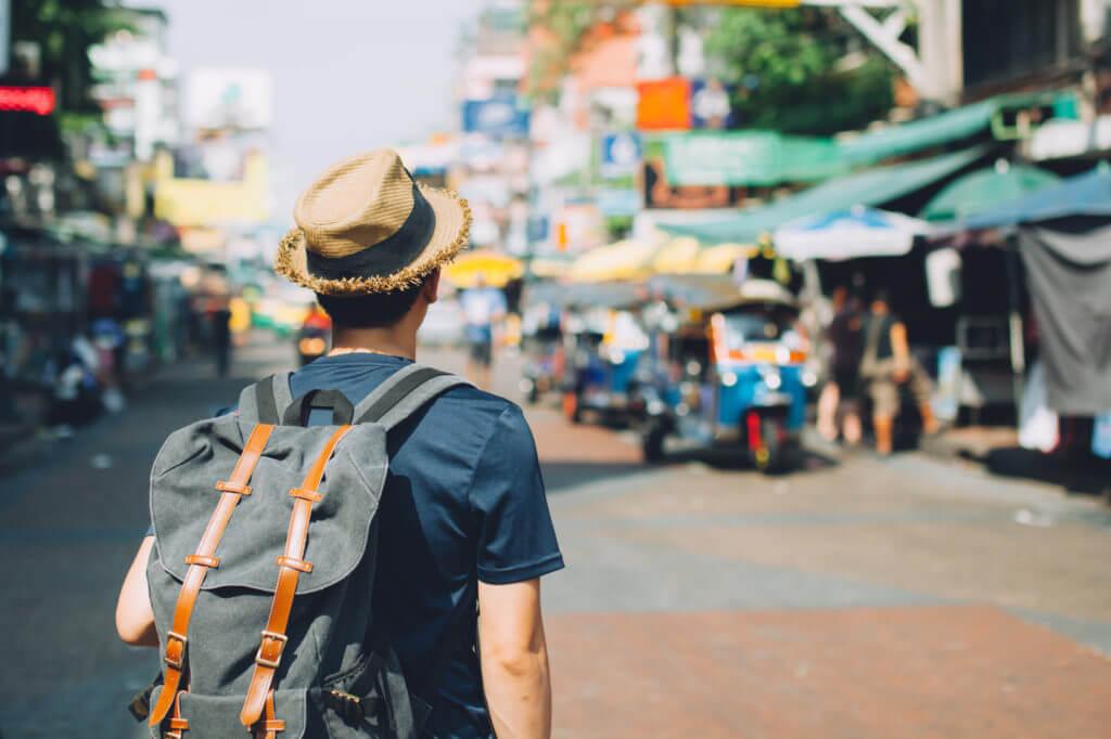 Backpack-Tourist mit Strohhut besucht Markt.