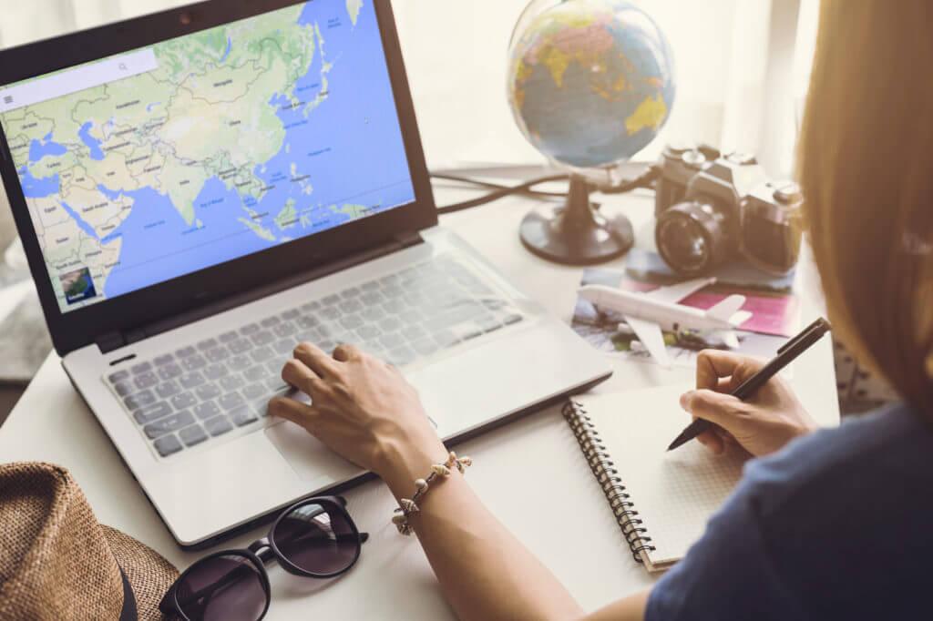 Frau schaut sich Weltkarte auf einem Laptop an.
