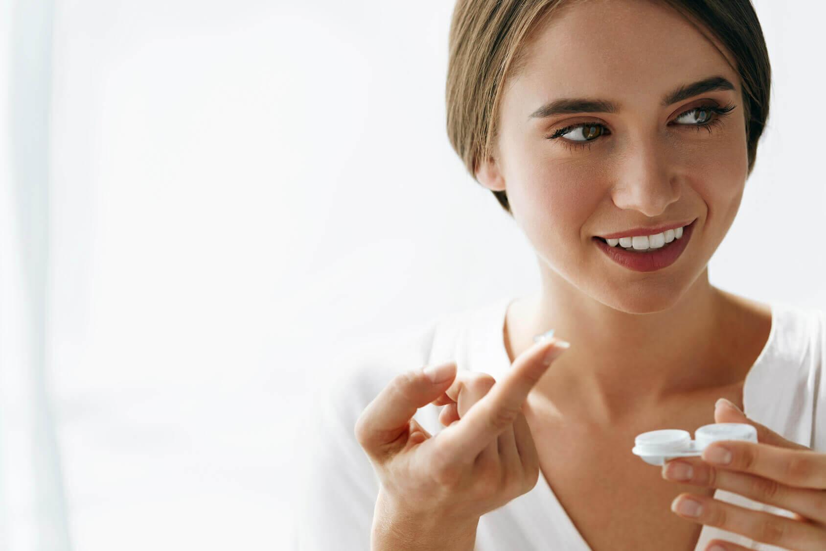 Frau hält Kontaktlinse.