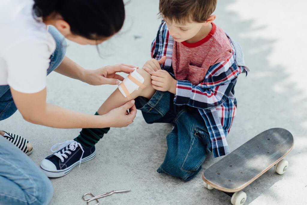 Frau verarztet Knie eines jungen Skateboardfahrers mit Pflaster.