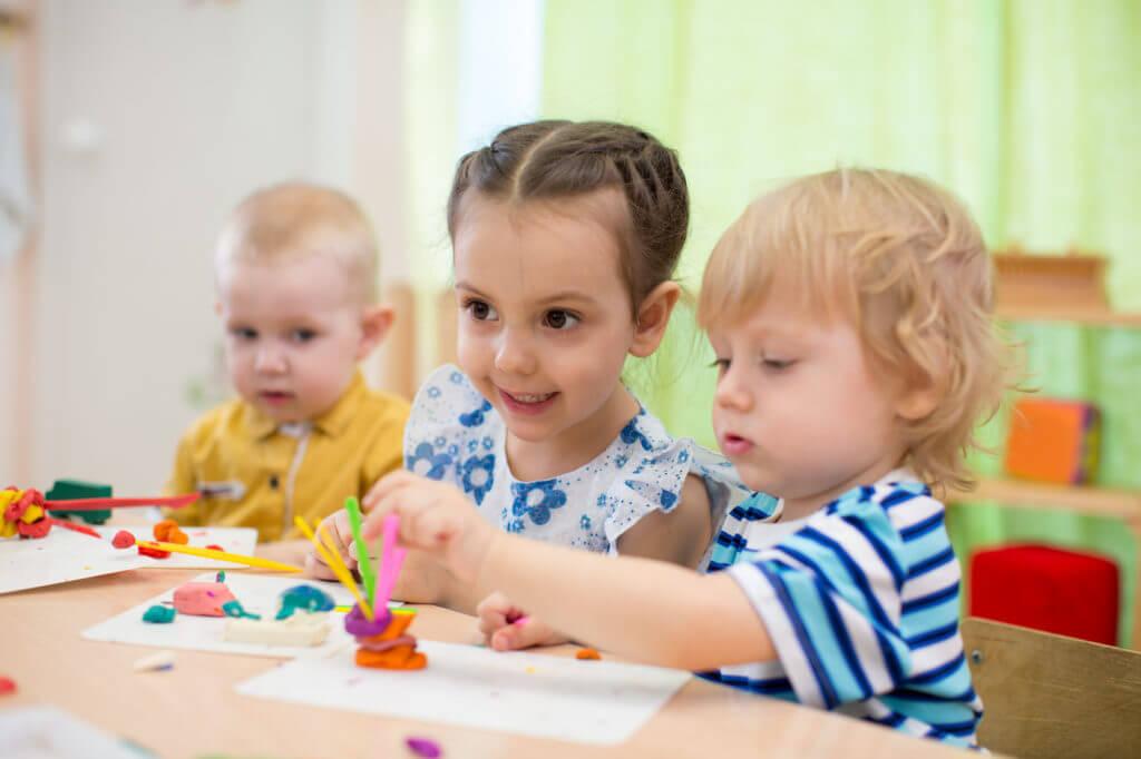 Kinder spielen mit Knete.