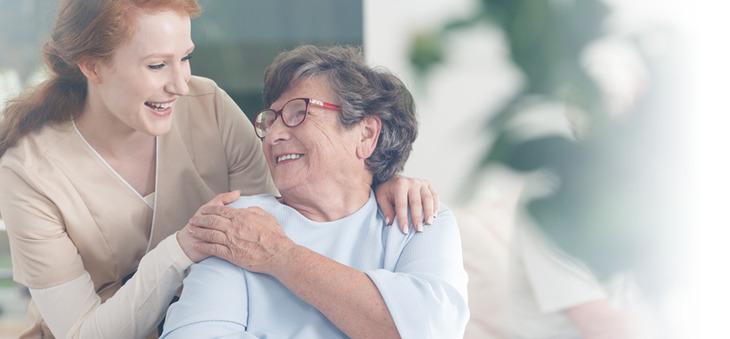 Seniorin berührt Hand einer jungen Frau.