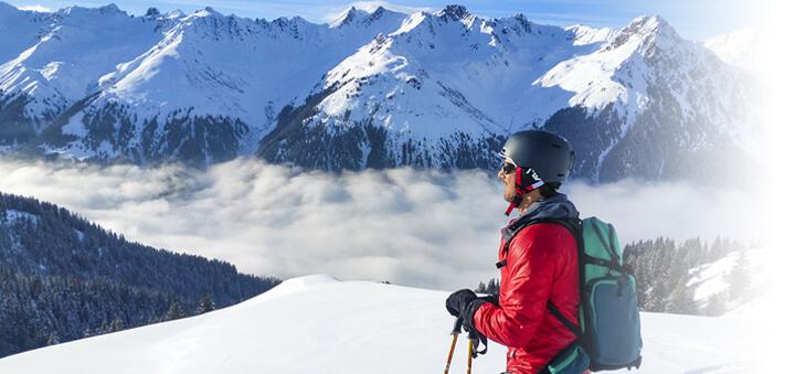 Wintersportler auf einem Gipfel vor Bergpanorama.