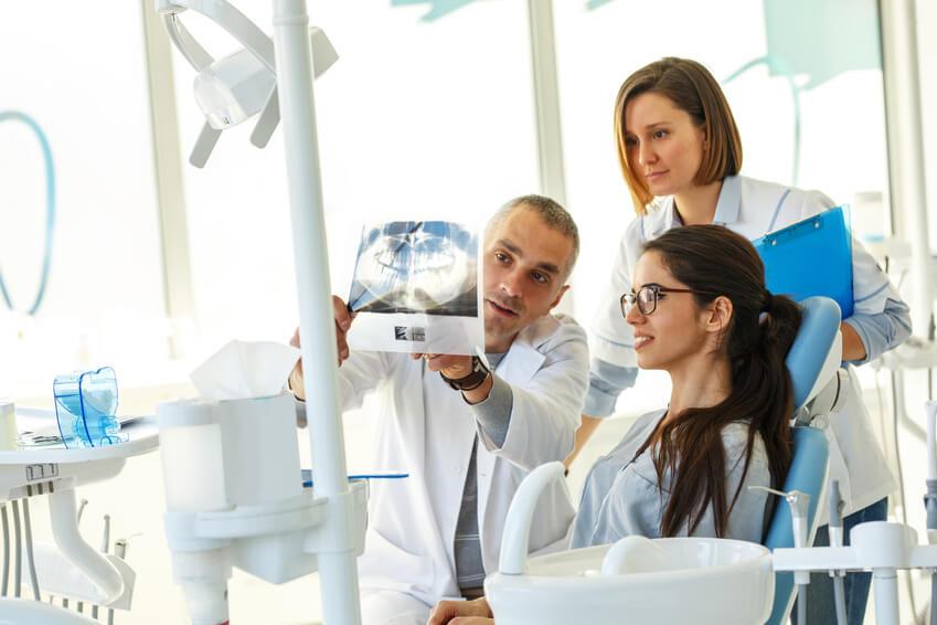 Zahnarzt erläutert Patientin und Zahnarztgehilfin ein Röntgenbild.