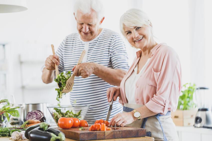 Älteres Paar bereitet Salat zu.