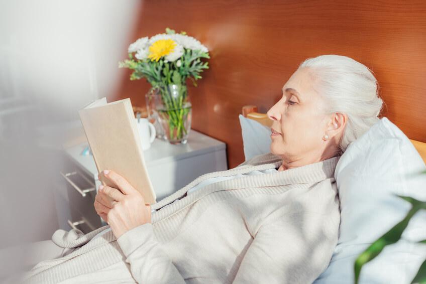 Lesende ältere Dame im Krankenhausbett.