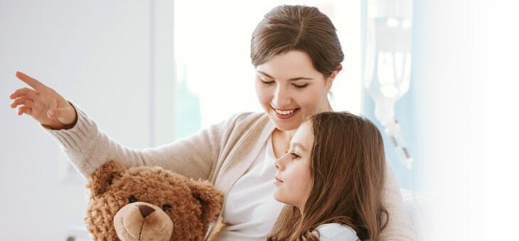 Frau umarmt Mädchen am Tropf mit Teddybär.