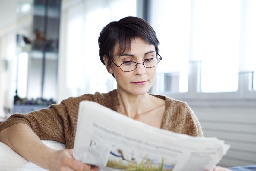 Frau mit Brille liest Zeitung.