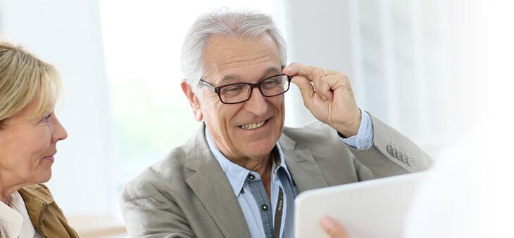 Mann probiert Brille und lächelt.