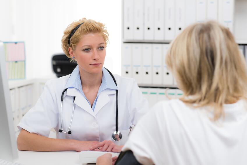 Ärztin und Patientin sitzen einander gegenüber.