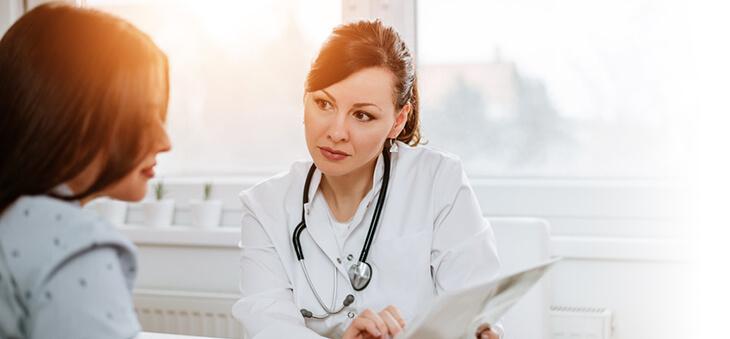 Ärztin und Patientin blicken auf ein Tablet-Display.