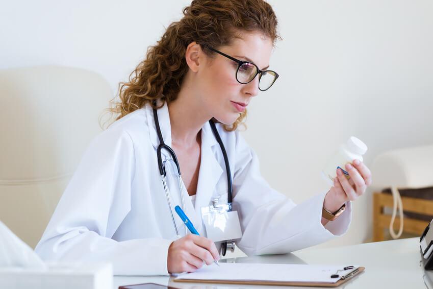 Ärztin hält Präparat in der Hand und schreibt mit Stift auf Klemmbrett.