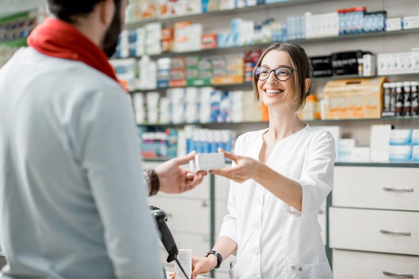 Apothekerin übergibt Medikament an Kunden.