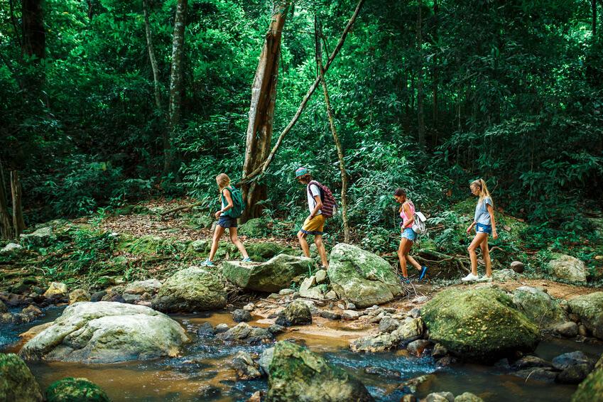 Touristengruppe überquert einen Fluss im Dschungel.