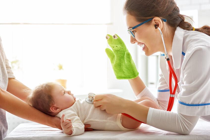 Ärztin zeigt Baby eine Handpuppe und hört es dabei an der Brust mit einem Stetoskop ab.