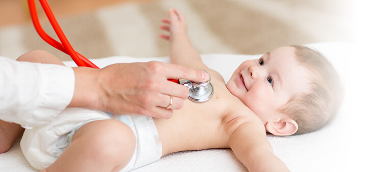 Baby wird an der Brust mit Stetoskop abgehört.