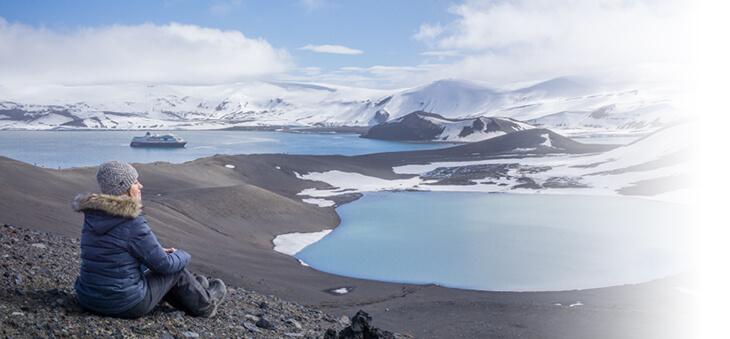 Frau sitzt in arktischer Landschaft vor verschneiten Hügeln und Wasser.