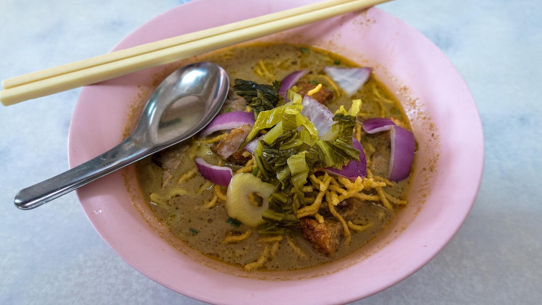 Asiatische Spezialität - Khao Soi mit Löffel und Stäbchen.