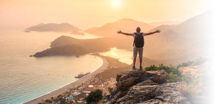 Mann steht mit ausgebreiteten Armen auf einem Berg und blickt über eine Stadt und auf das Meer.