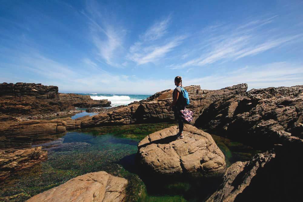 Backpackerin steht in Felslandschaft am Meer im Tsitsikamma National Park Südafrika.