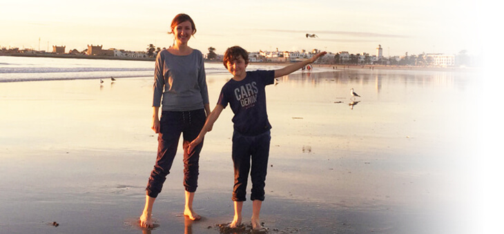 Frau und Junge posieren lächelnd am Strand.