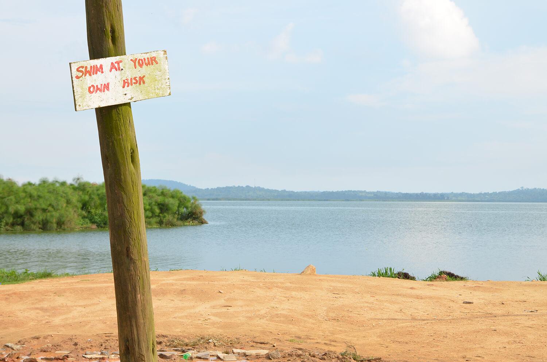 """Schild mit der Aufschrift """"Swim at your own risk"""" steht an Seeufer."""