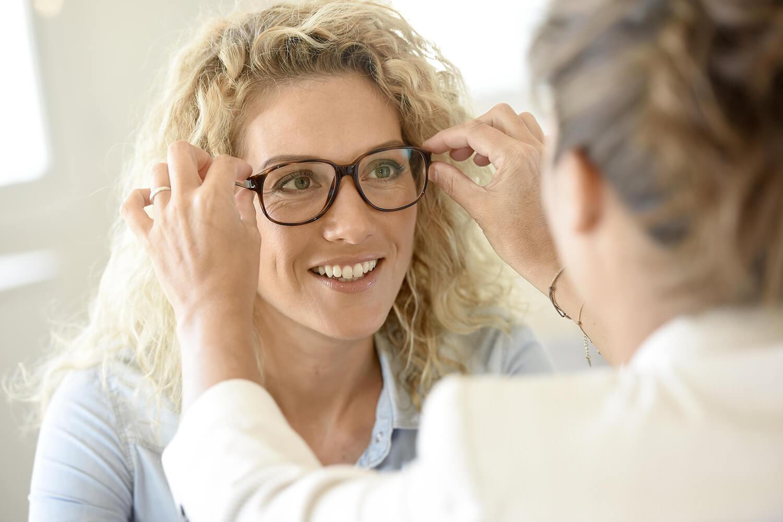 Frau lässt Brille von Optikerin anpassen.