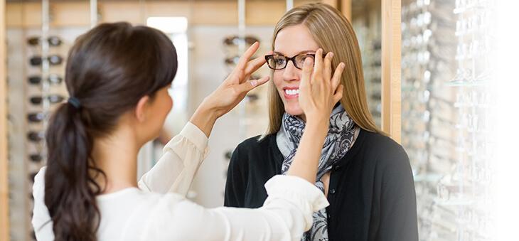 Optikerin passt Brille für Kundin an.