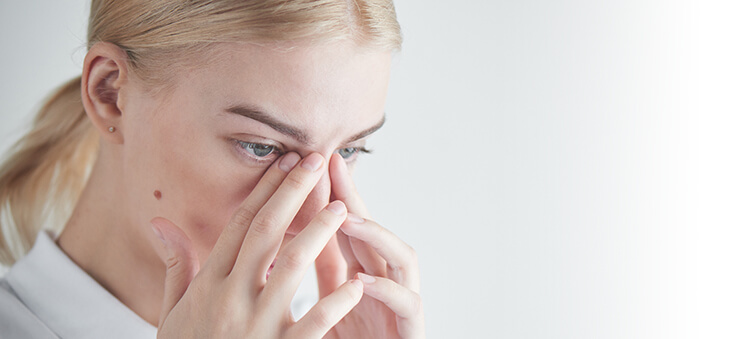 Frau tastet mit den Fingern zwischen Augen und Nasenwurzel.