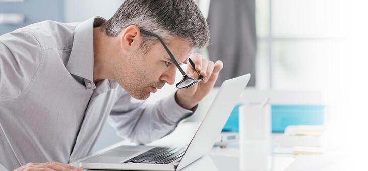 Mann versetzt Brille vor dem Laptop-Bildschirm.