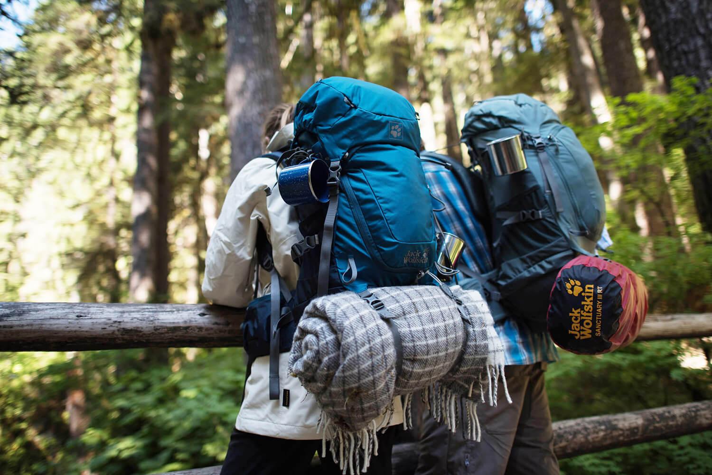 Zwei Backpacker im Wald mit Rucksäcken und Schlafsäcken.