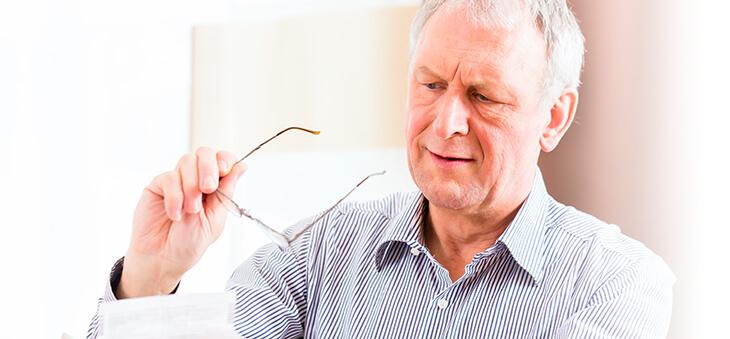 Älterer Mann hält Brille in der Hand.