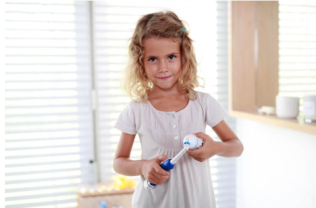 Kind trägt Zahncreme auf elektrische Zahnbürste auf.