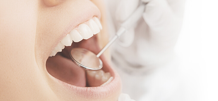 Zahnarzt führt kleinen Spiegel in geöffneten Mund.