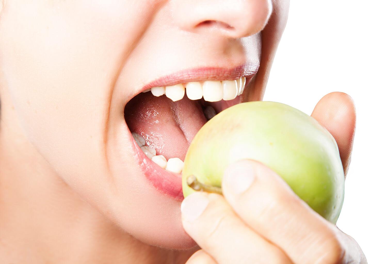 Junge Frau beißt in einen Apfel.