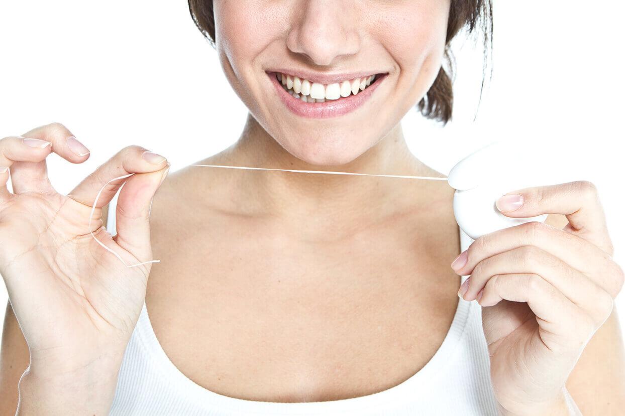 Frau hält Zahnseide in den Händen.
