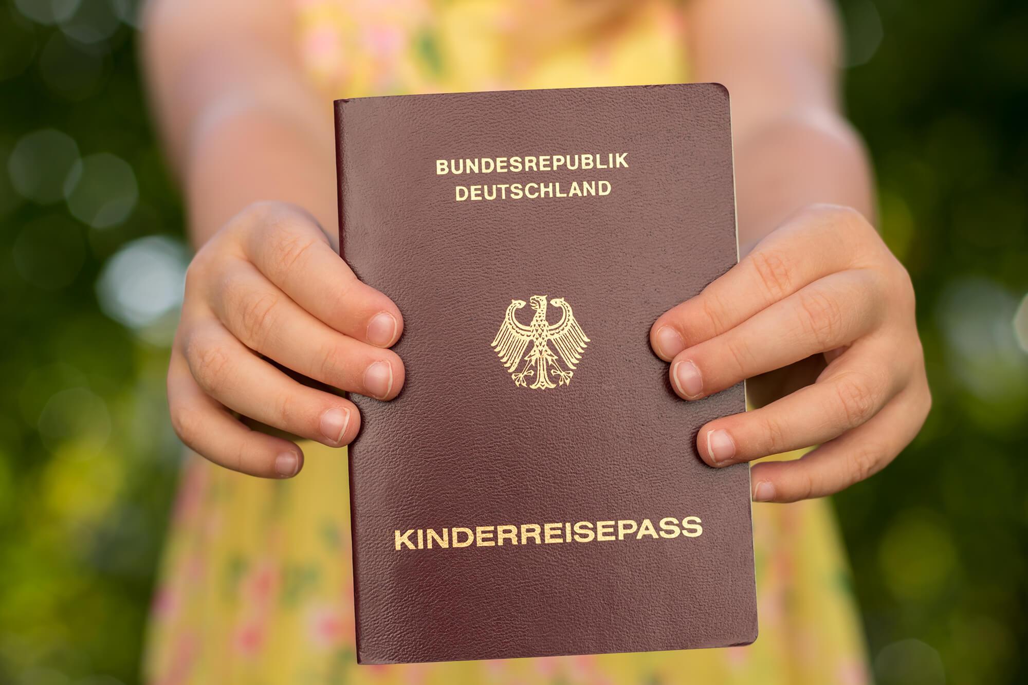 Kind hält einen deutschen Kinderreisepass.