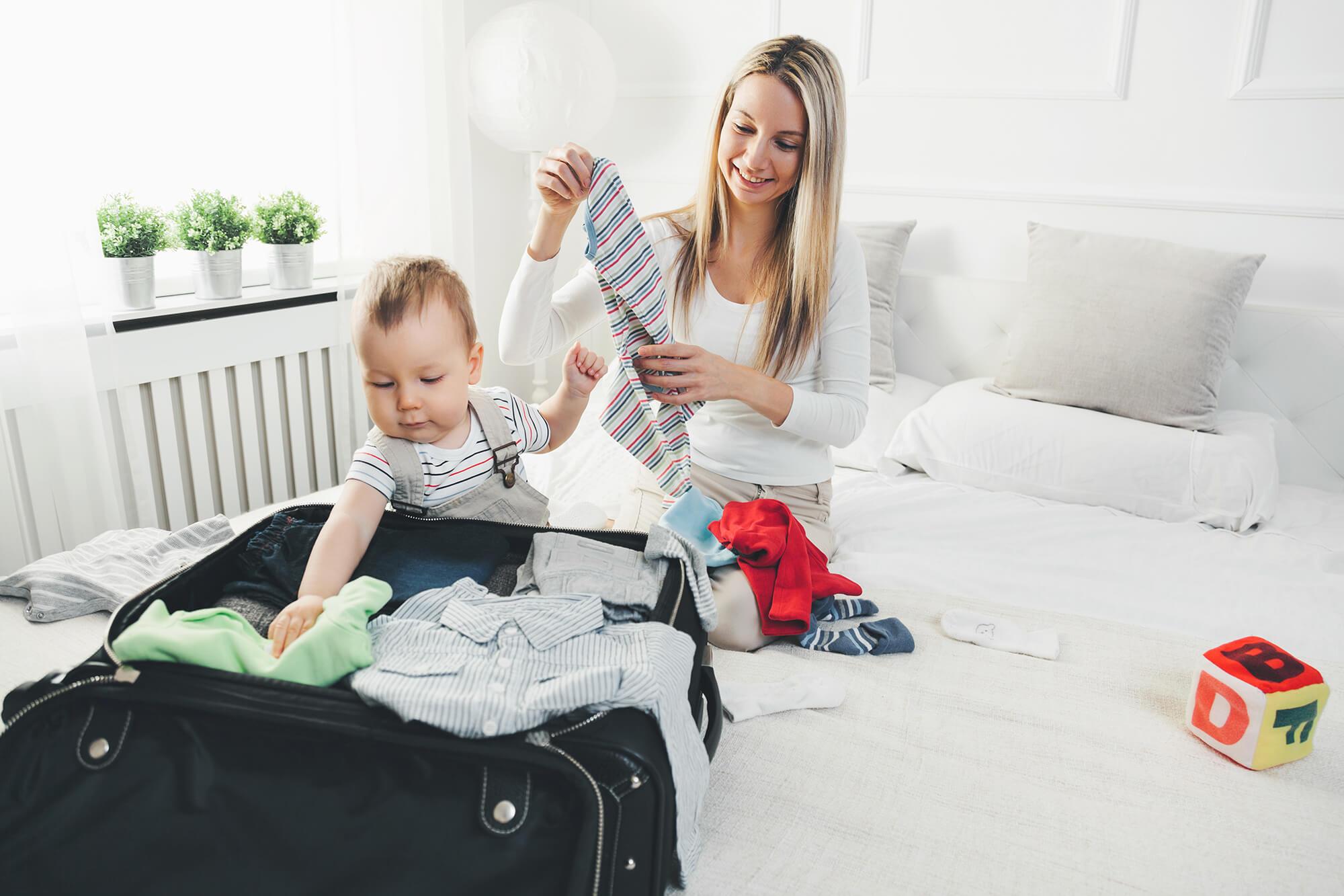 Mutter und Kleinkind packen Koffer.