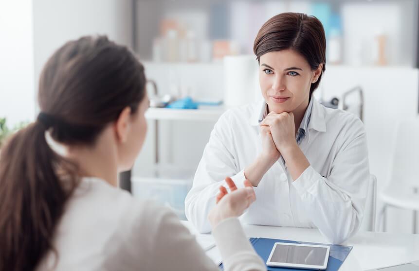 Patientin spricht mit Ärztin und lächelt.