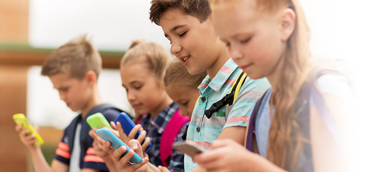 Kinder blicken auf Smartphones.