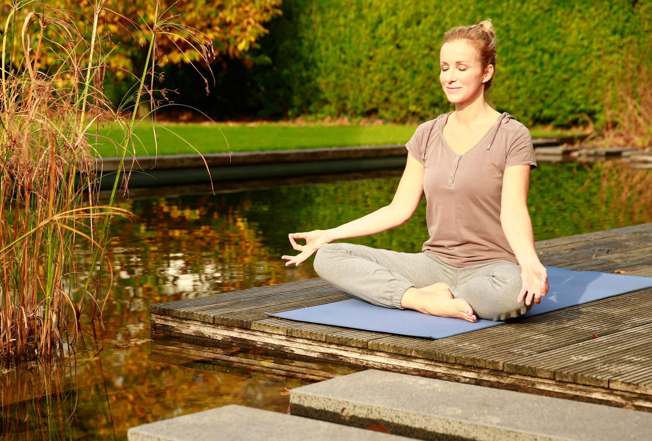 Frau meditiert am Wasser.