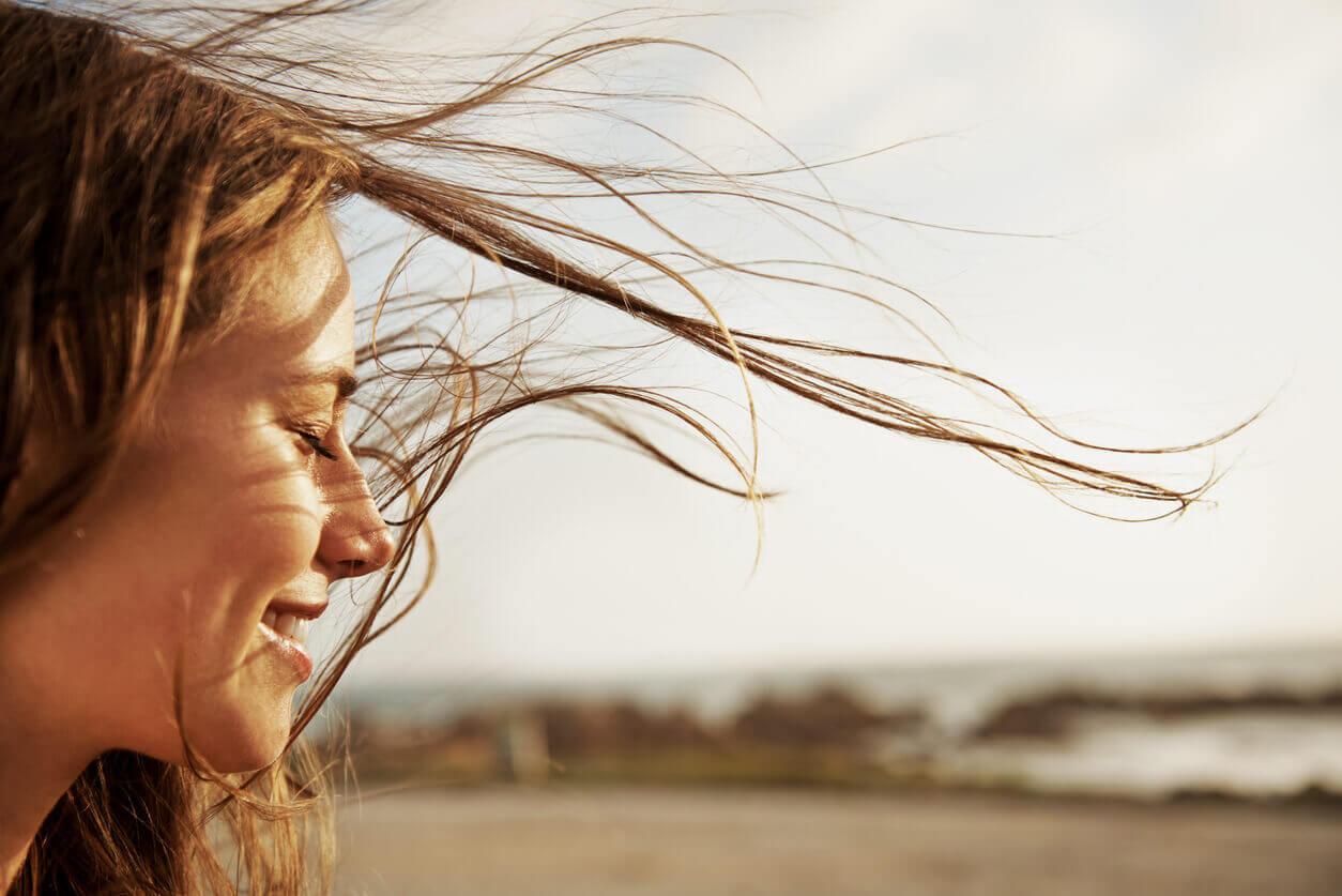 Frau mit geschlossenen Augen genießt den Wind.
