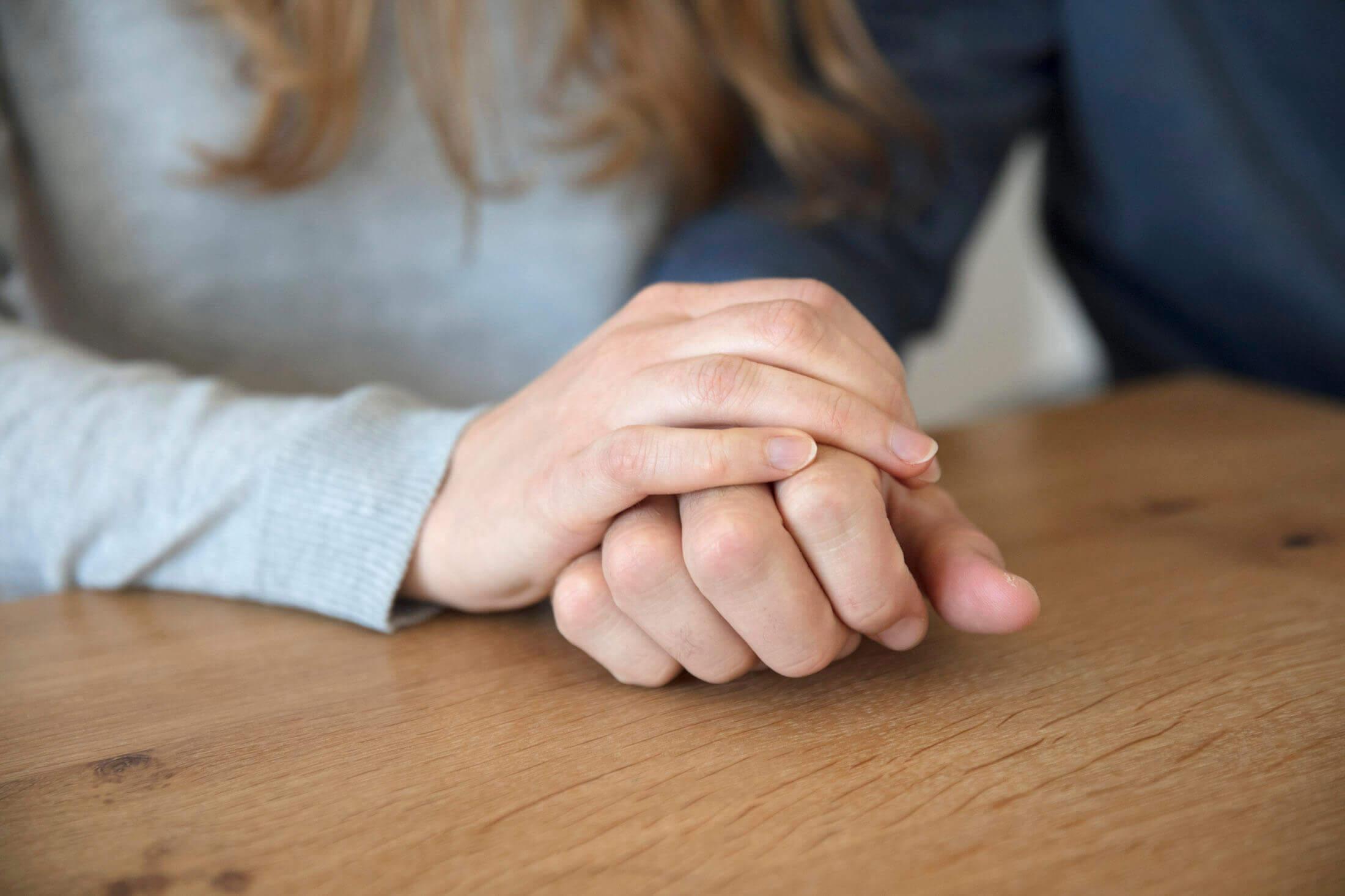 Frau legt ihre Hand auf die Hand eines Mannes.