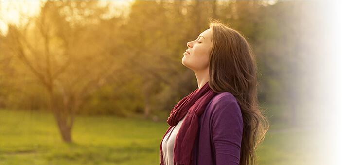 Frau atmet tief ein und entspannt.