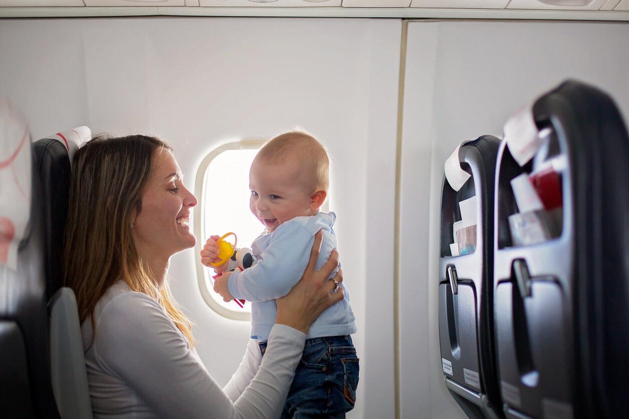 Mutter spielt im Flugzeug mit Kleinkind.