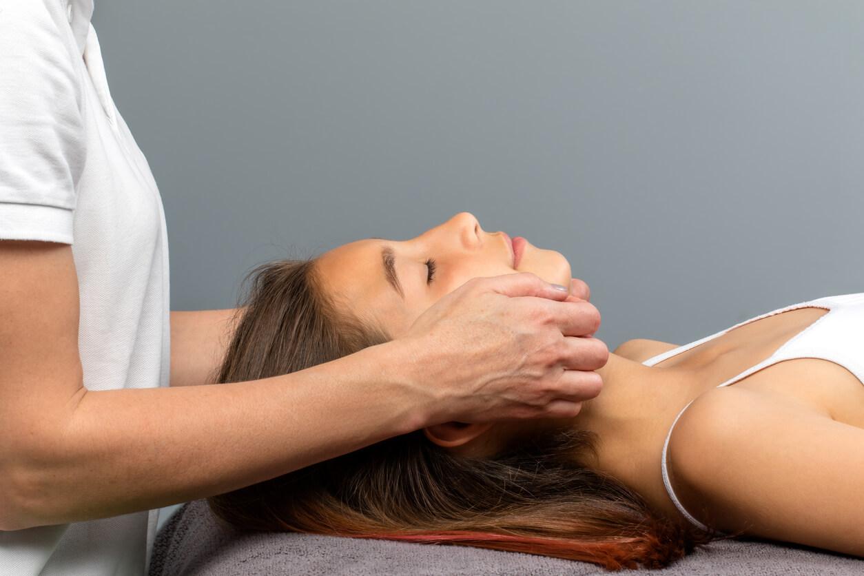Heilpraktikerin setzt Hände am Gesicht einer entspannt liegenden Patientin an.